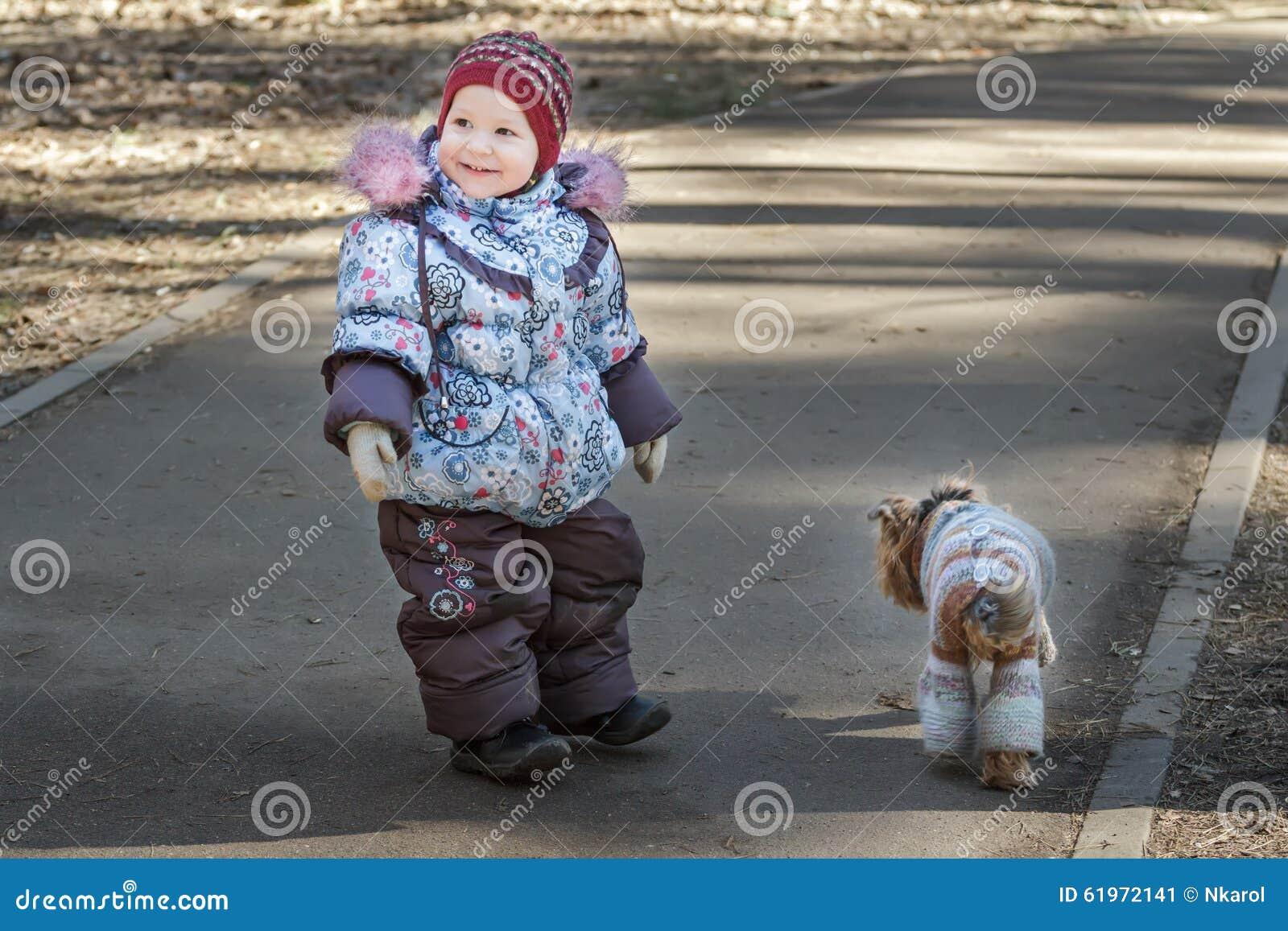 La niña pequeña sonriente que caminaba con su compañero canino se vistió en capa hecha punto azul en parque del tiempo frío
