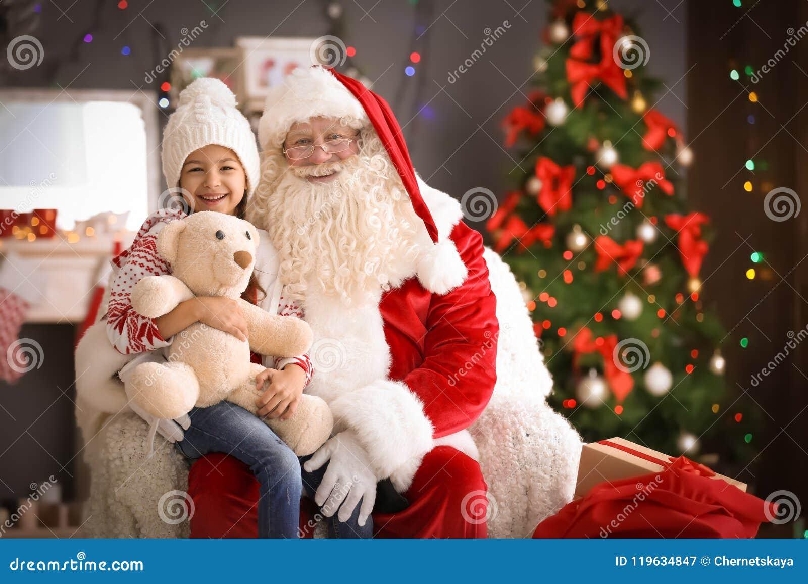 La niña que se sienta en el ` auténtico de Santa Claus traslapa dentro