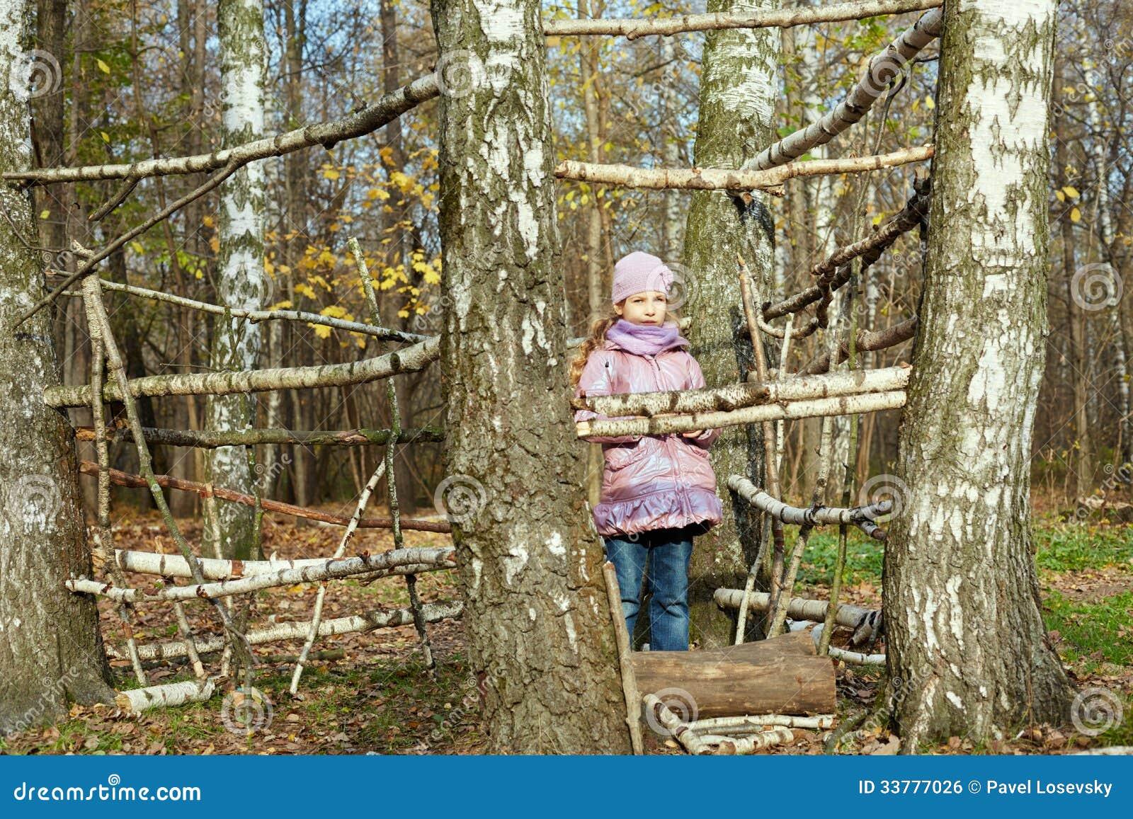 La niña se coloca en parque del otoño dentro del marco