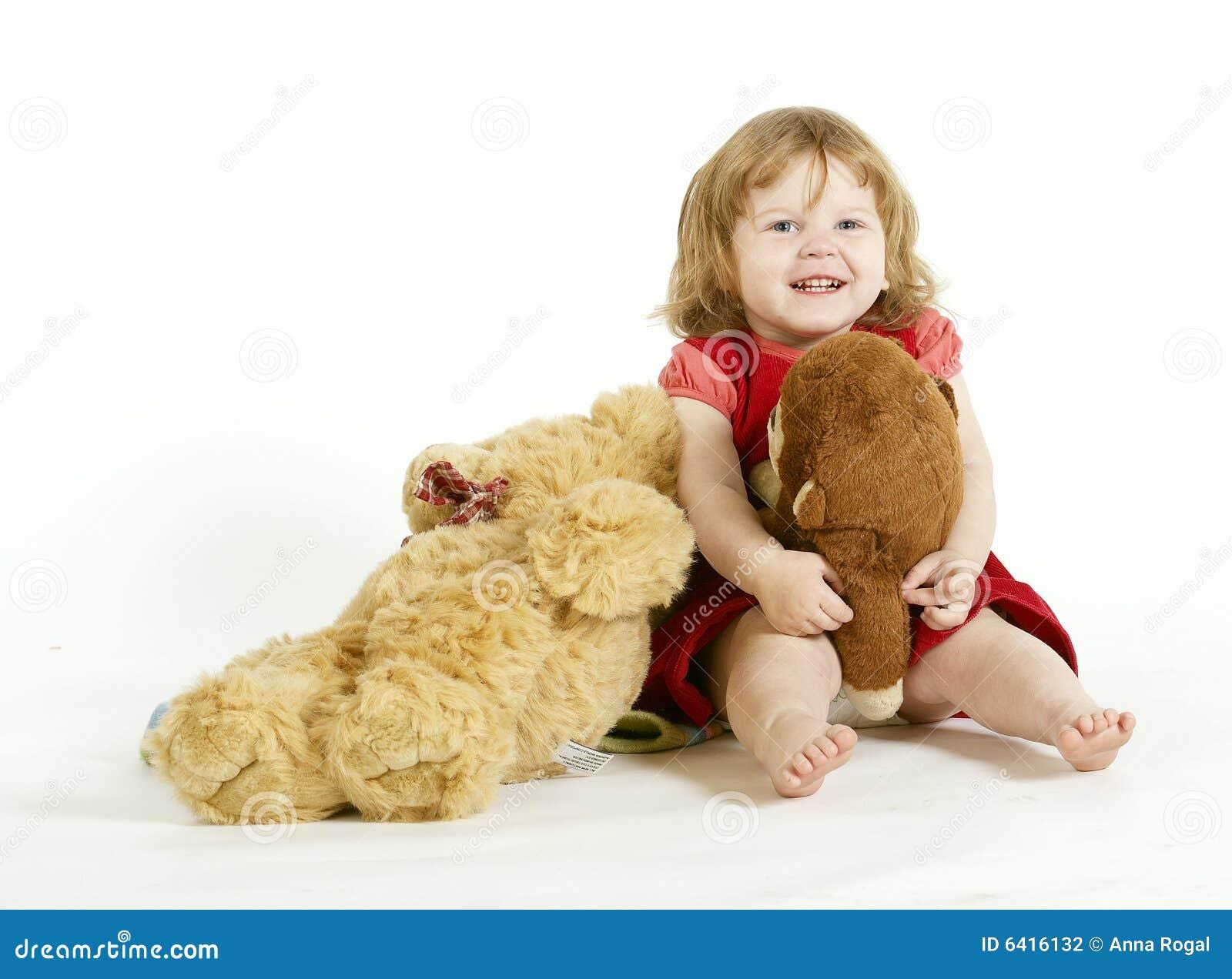 La niña sonriente con los juguetes de la felpa.