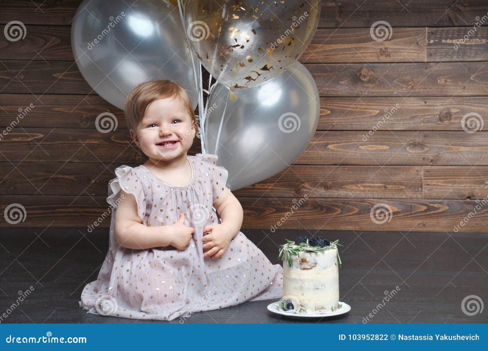 La niña sonriente linda celebra su primera fiesta de cumpleaños con los globos y la torta