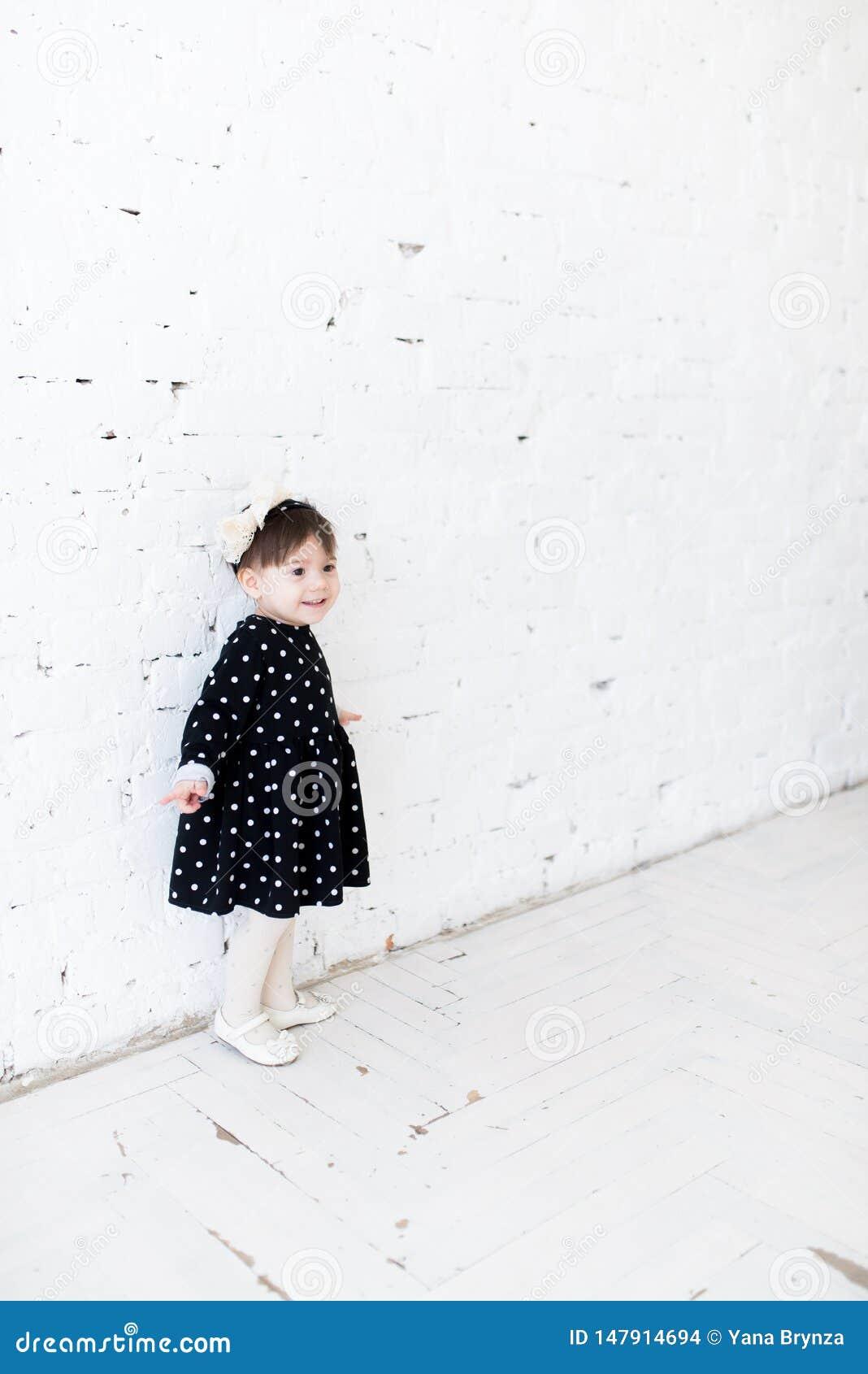 La ni?a hermosa en un vestido del lunar se est? colocando cerca de la pared de ladrillo y de la sonrisa blancas Celebraci?n del c