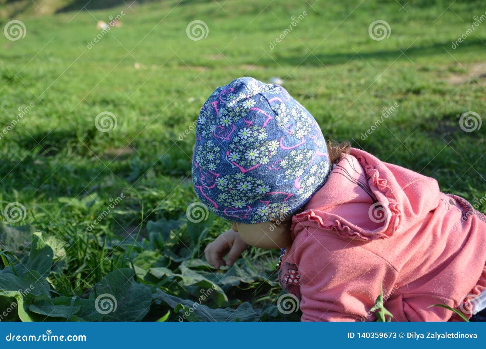 La ni?a juguetona linda sonriente se est? colocando en hierba verde la muchacha que el ni?o camina alrededor del lago aprende cam