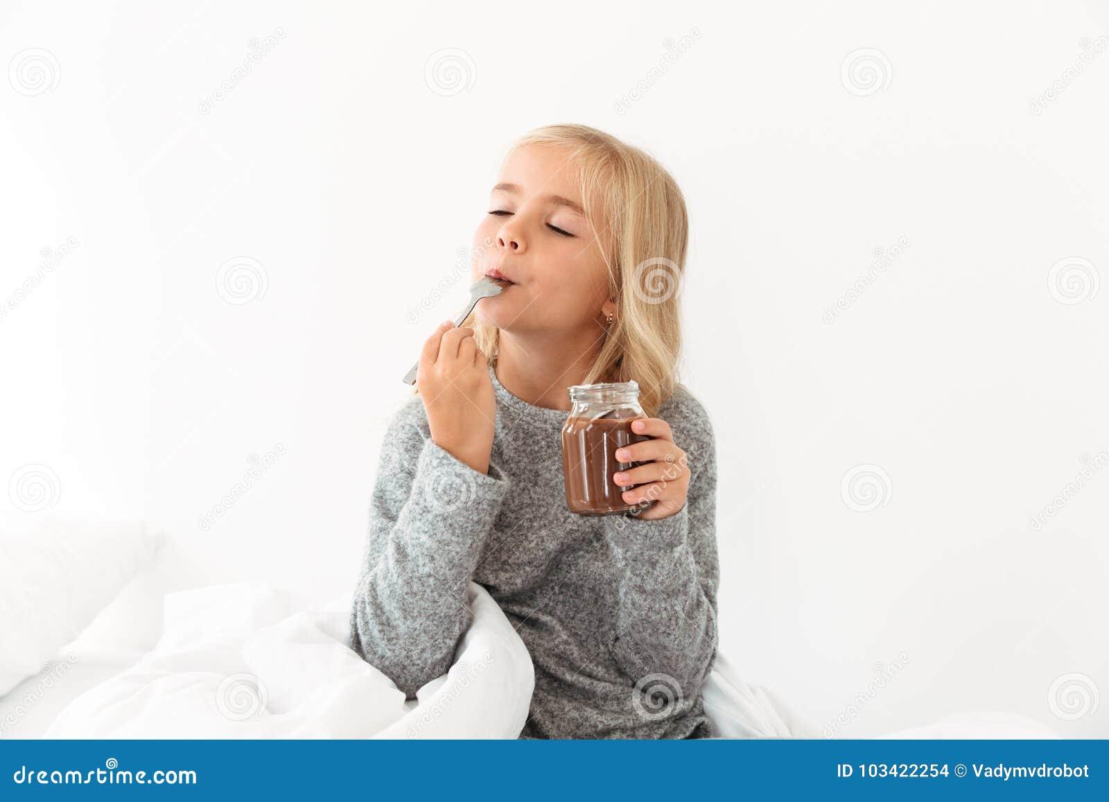 La nocciola joying del cioccolato della ragazza bionda sveglia si è sparsa con ey chiuso