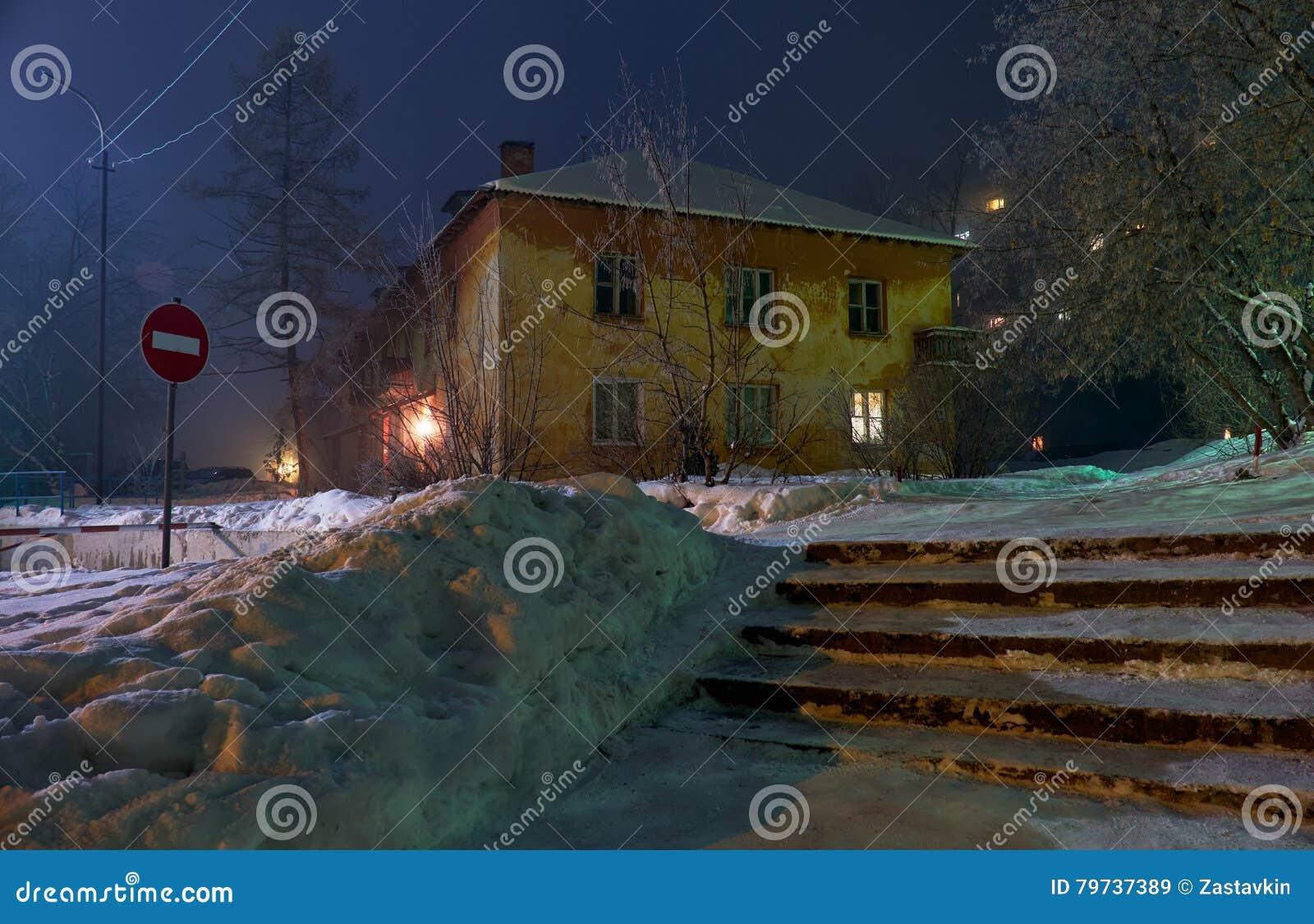 La noche tiró de la calle debajo de nieve con la casa residencial vieja en los wi