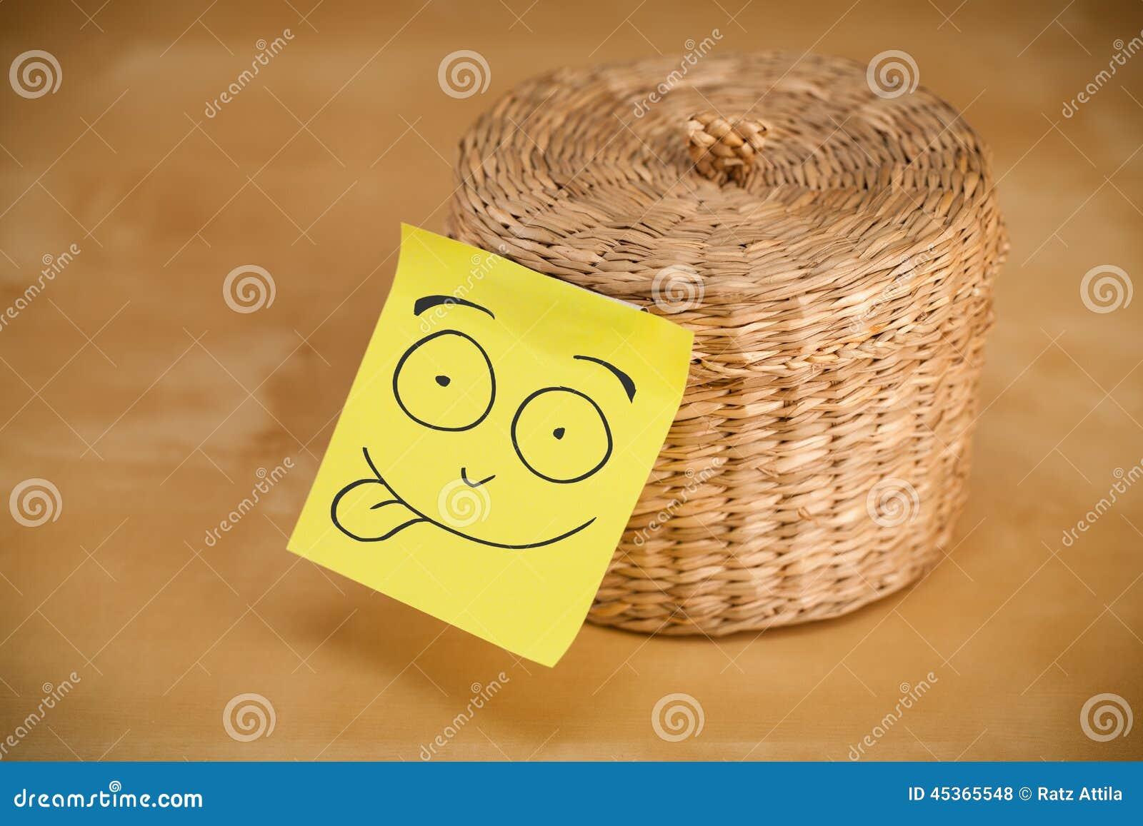 La note de post-it avec le visage souriant sticked sur une boîte à bijoux