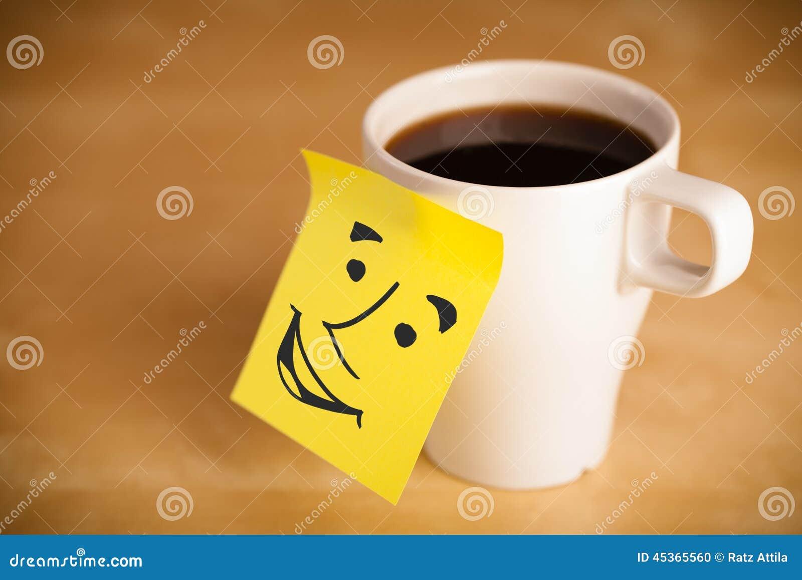 La note de post-it avec le visage souriant sticked sur une tasse