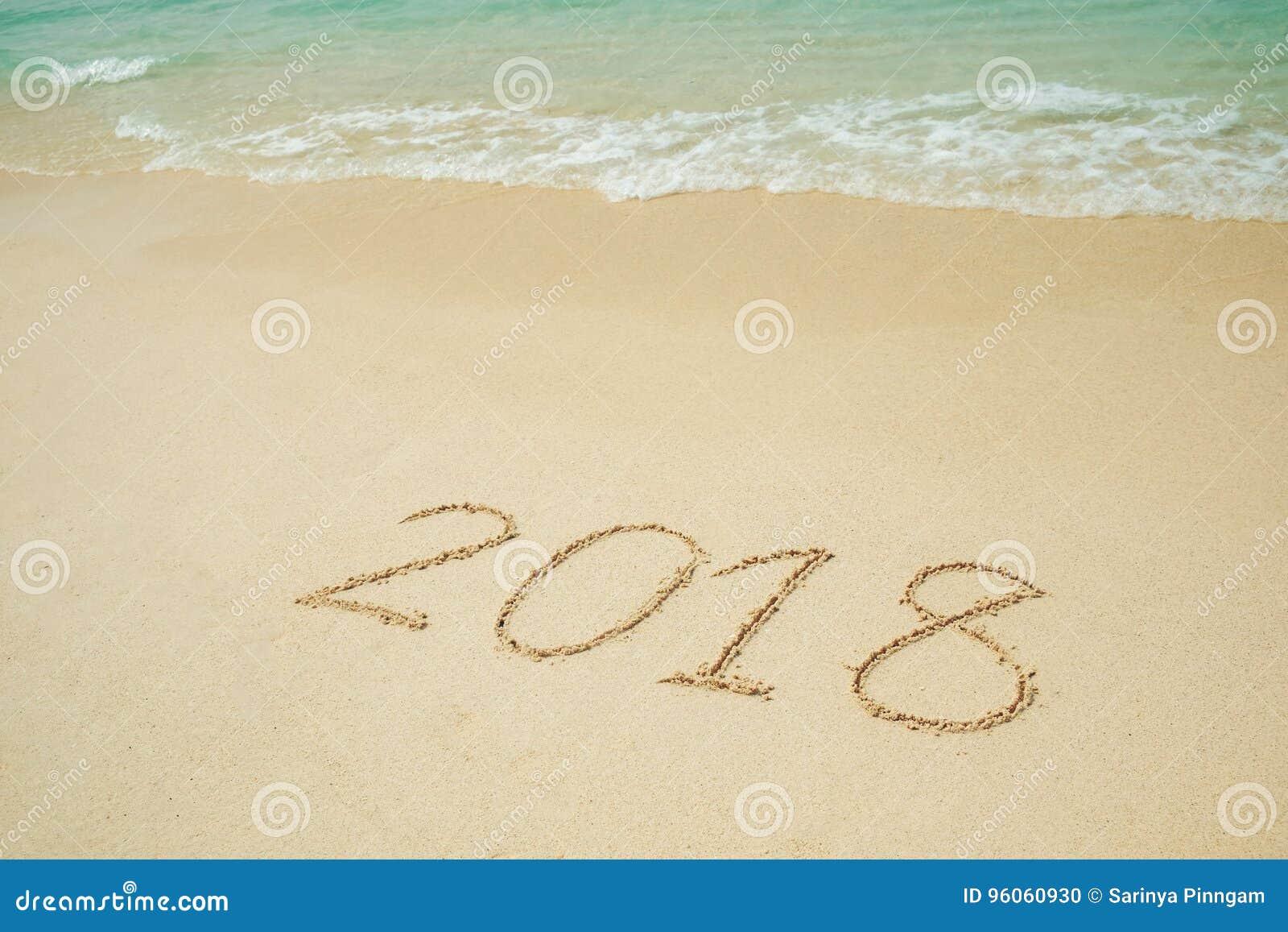 La nouvelle année 2018 vient 2018 sur un sable de plage, la vague