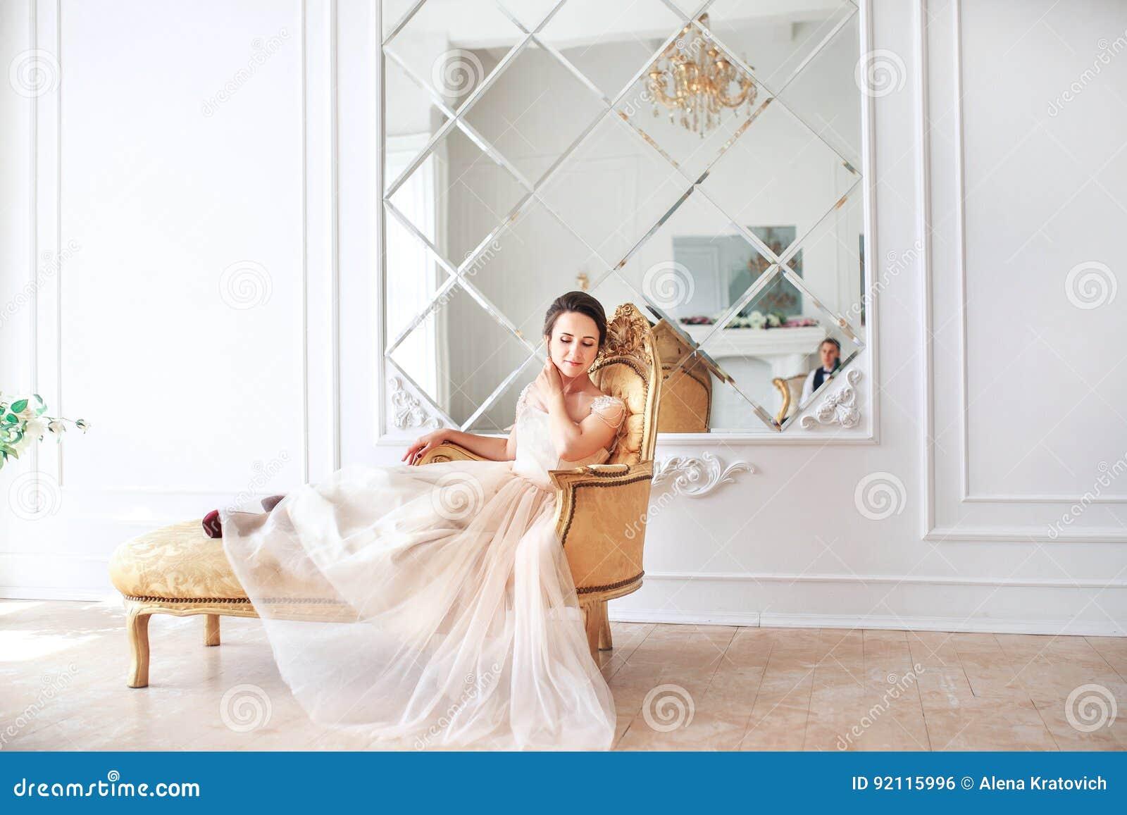La novia en el vestido hermoso que se sienta en el sofá dentro en el interior blanco del estudio tiene gusto en casa Estilo de mo
