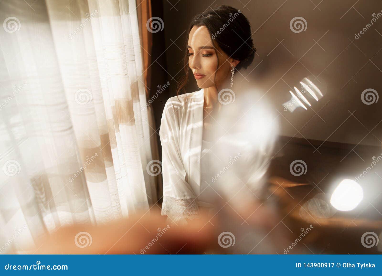 La novia en el vestido hermoso que se sienta en silla dentro en el interior blanco del estudio tiene gusto en casa Tiro de moda d