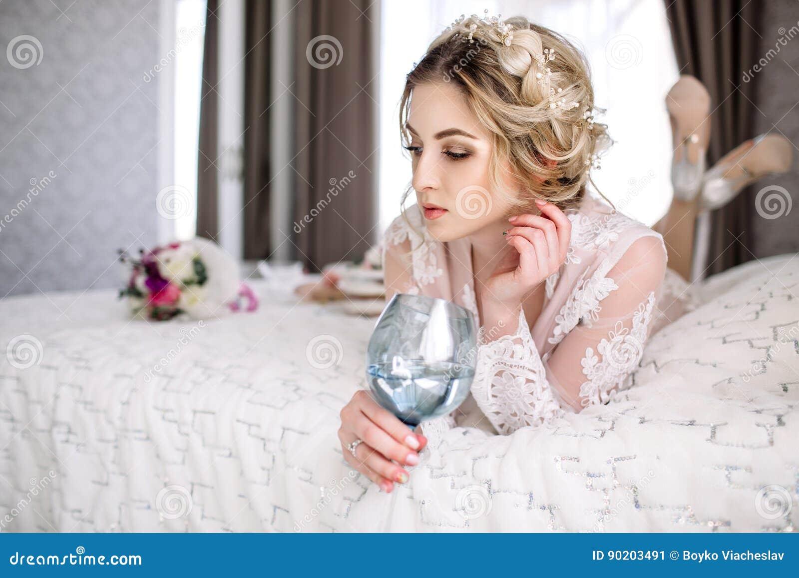 La novia en una albornoz a la ventana del dormitorio por la mañana