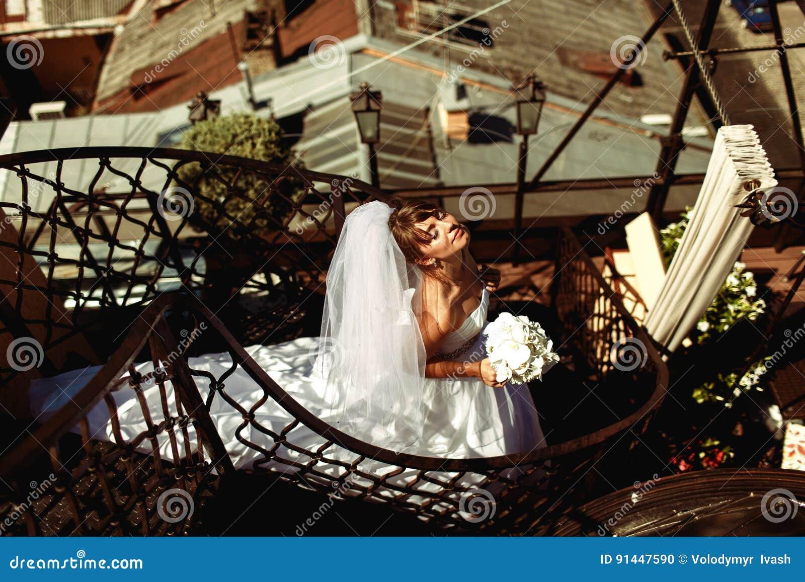 La novia goza del sol del verano que se coloca en las escaleras espirales en el roo