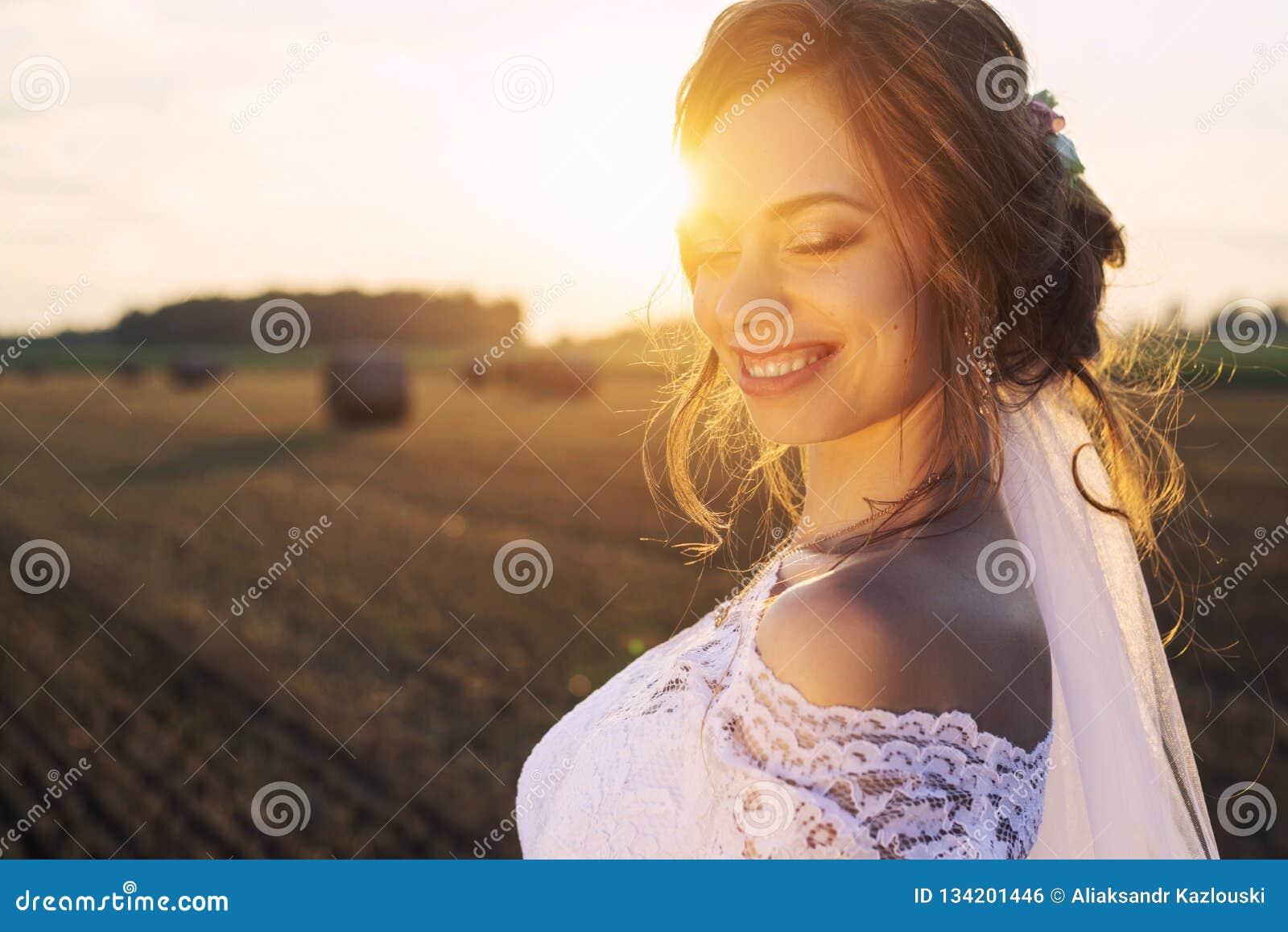 La novia hermosa en un vestido del cordón está sonriendo en el fondo de la naturaleza