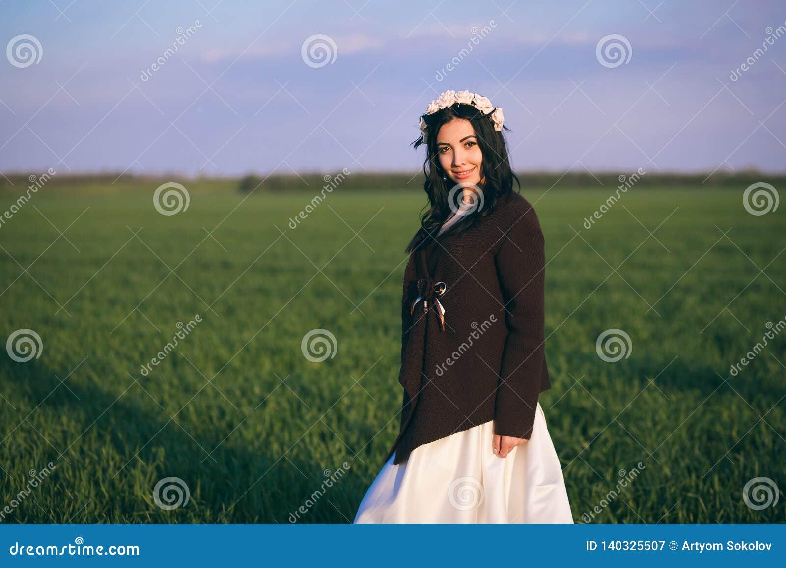 La novia se está colocando en un campo en la puesta del sol, llevando un suéter hecho punto, una tarde fría