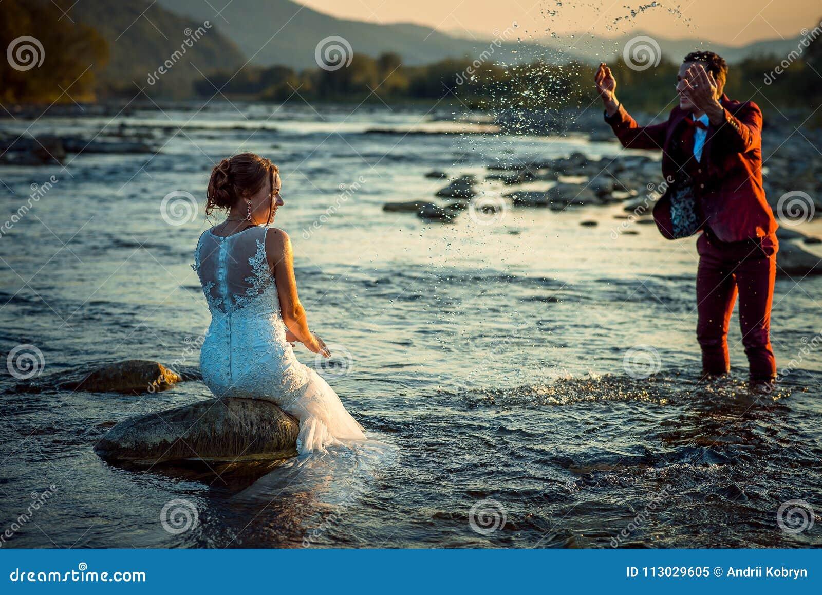 La novia se está sentando en la piedra del río mientras que su novio hermoso está salpicando el agua en ella durante la puesta de