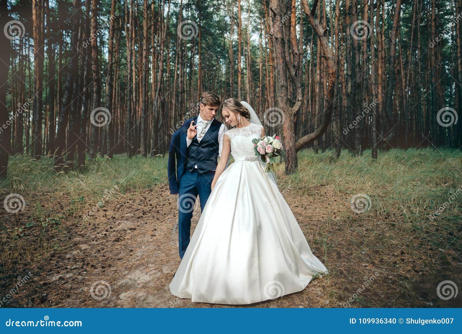La novia y el novio en vestidos de boda en fondo natural Nosotros