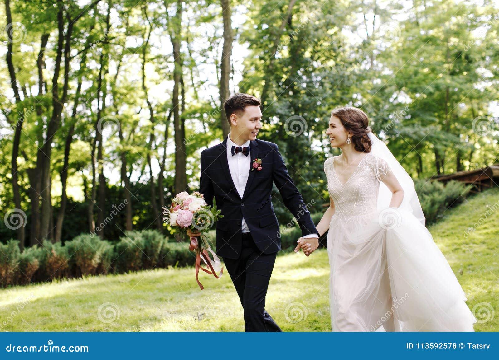 La novia y el novio felices de la sonrisa miran uno a y corriendo en el jardín verde El casarse en el verano en el parque Feliz