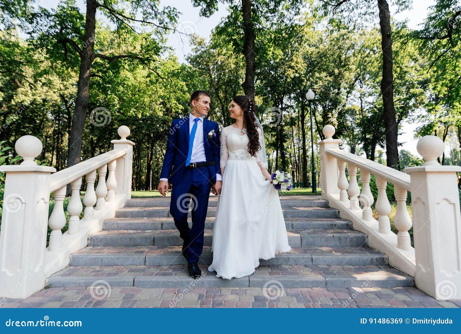 La novia y el novio que caminan abajo de las escaleras en el parque El novio abraza a la novia Pares de la boda en amor en el día
