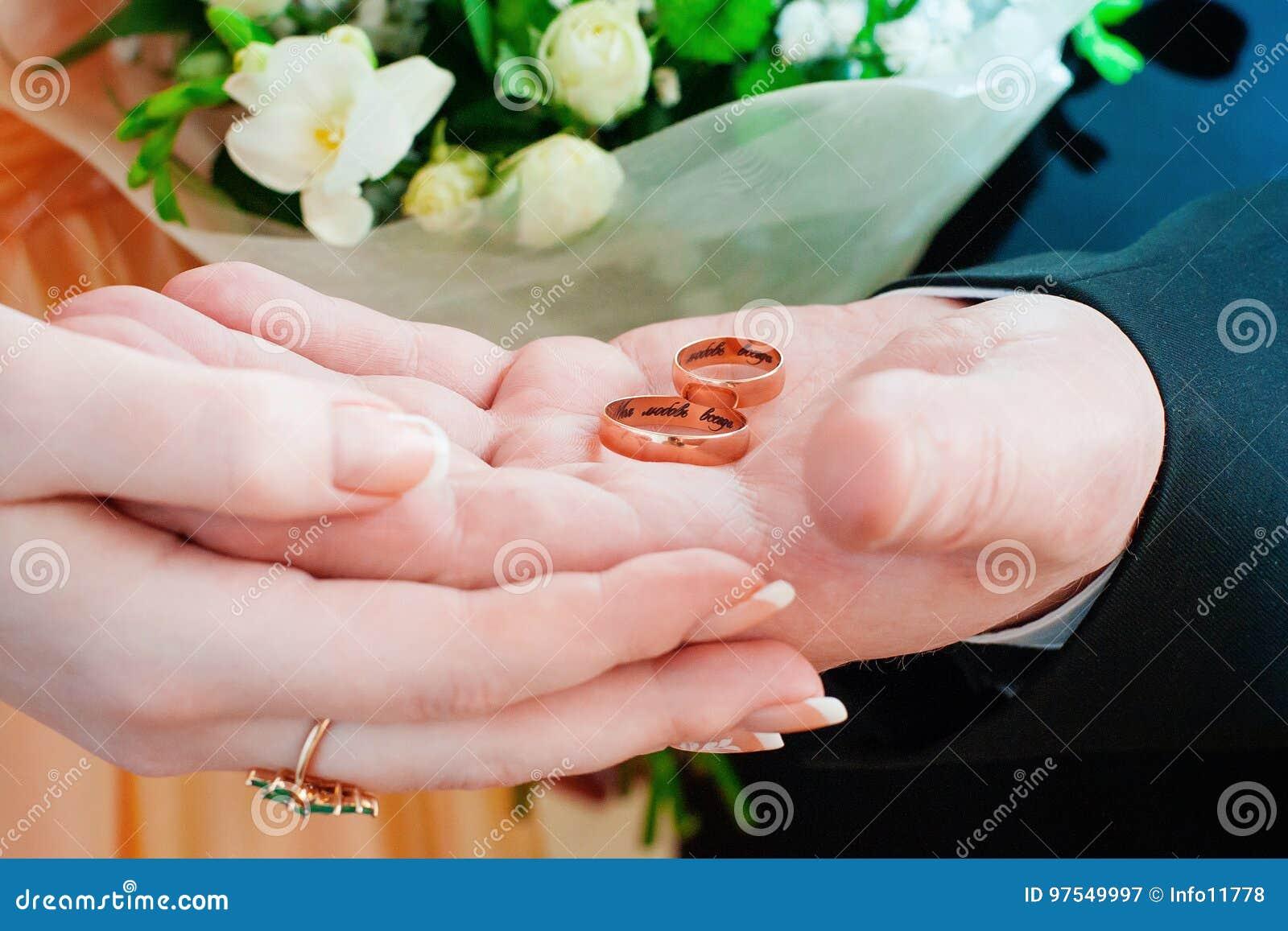 La novia y el novio que llevan a cabo los anillos