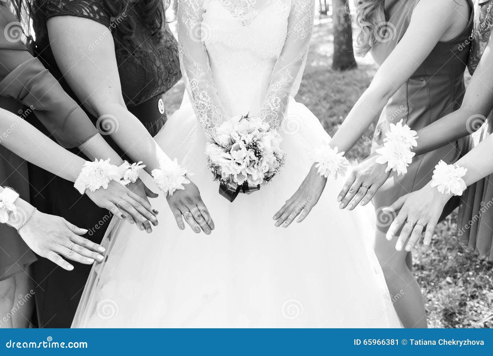 La novia y las damas de honor están mostrando las flores hermosas en sus manos