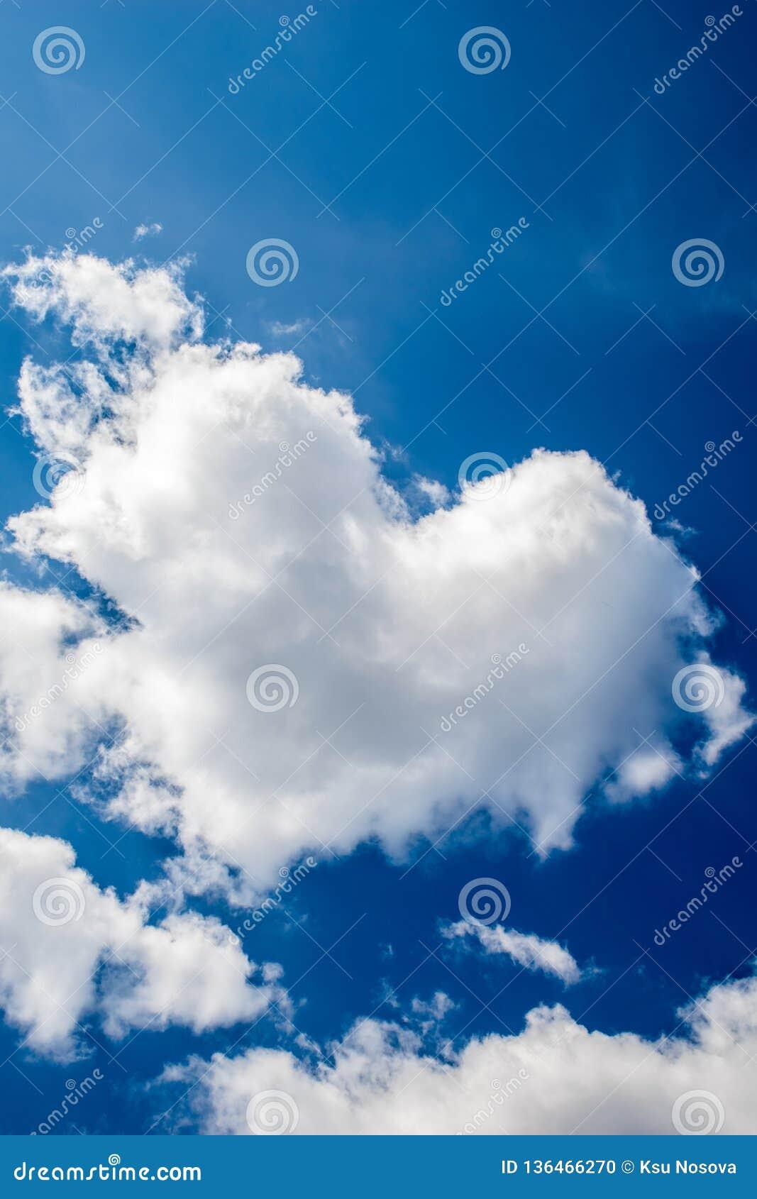 La nube bajo la forma de corazón contra un cielo azul Al día de tarjeta del día de San Valentín