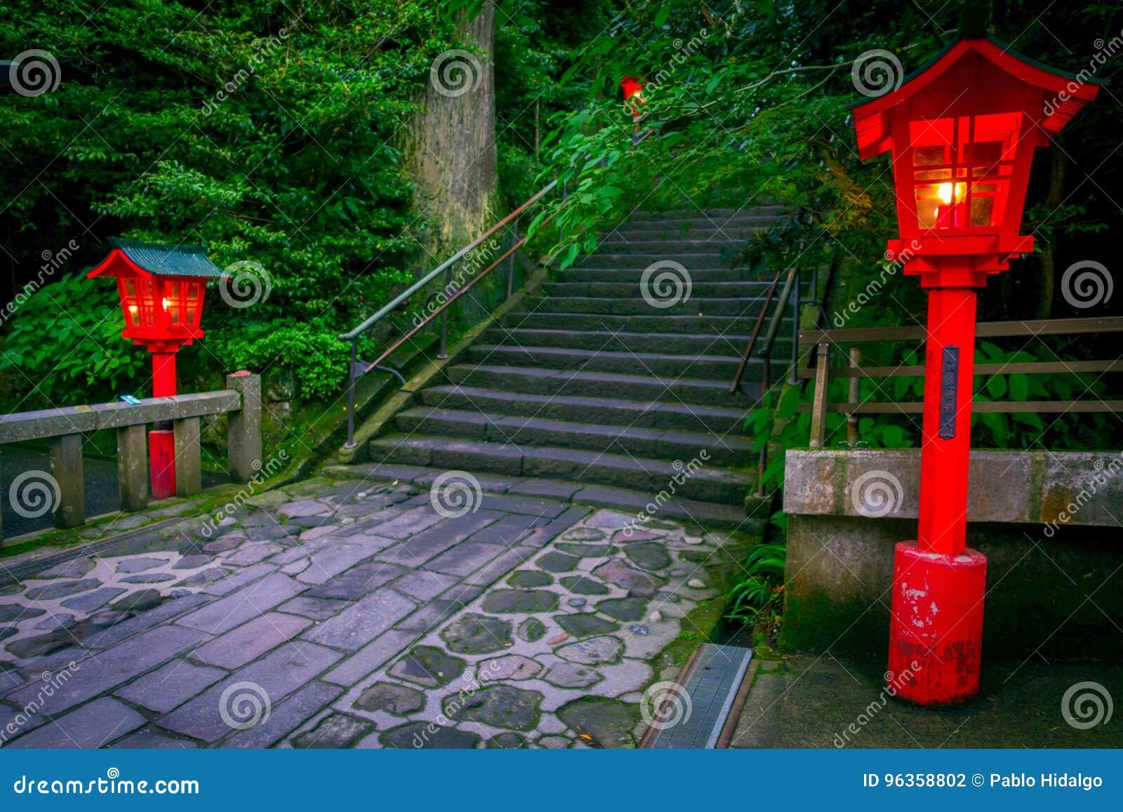 La opinión de la noche del acercamiento a la capilla de Hakone en un bosque del cedro con muchos linterna roja encendida para arr