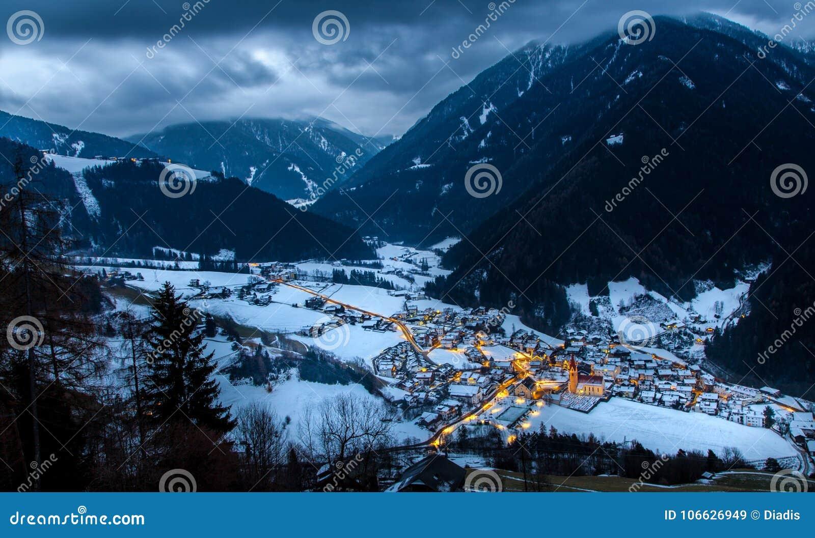 La opinión superior sobre pueblo nevoso luesen el valle en la noche el Tirol del sur él