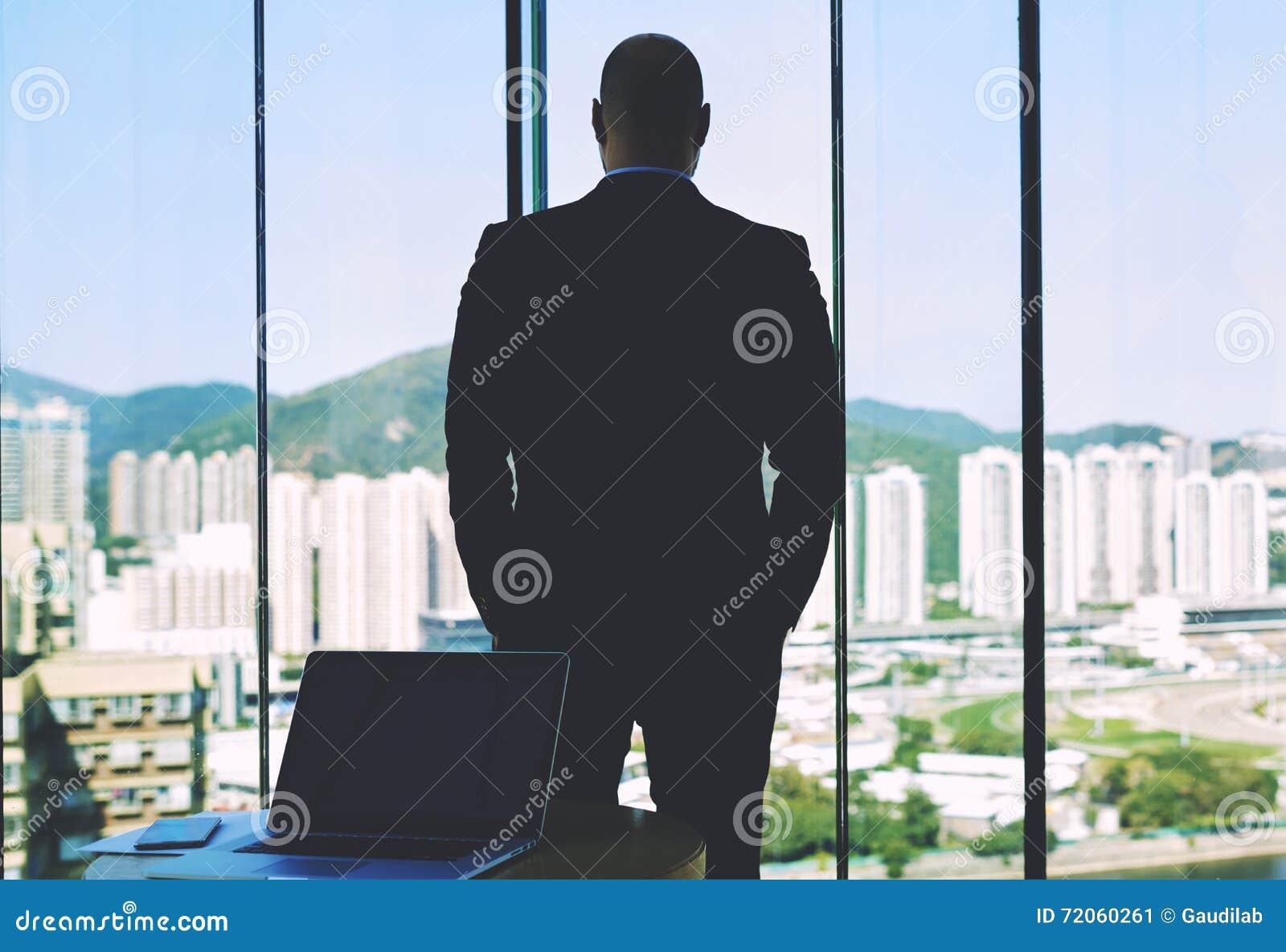 La opinión trasera un empresario confiado del hombre está mirando en ventana grande de la oficina