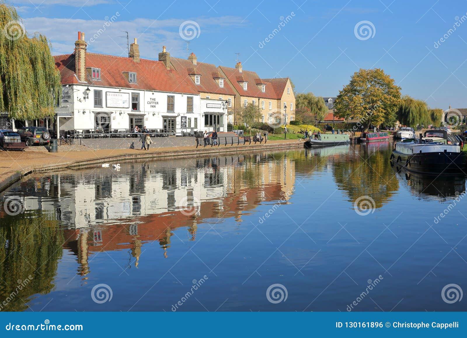 La orilla en otoño con las gabarras amarradas en el río Great Ouse y las casas tradicionales