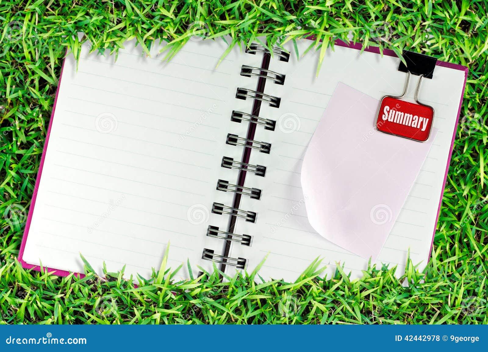 La página en blanco del cuaderno en hierba y la carpeta acortan