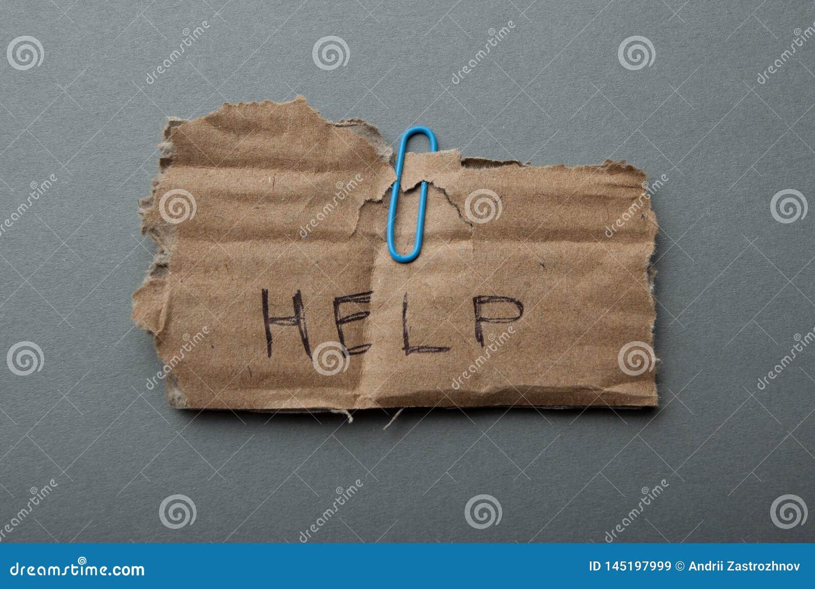 La palabra 'ayuda 'escrita en la cartulina, aislada en un fondo, una pobreza y una desesperación grises
