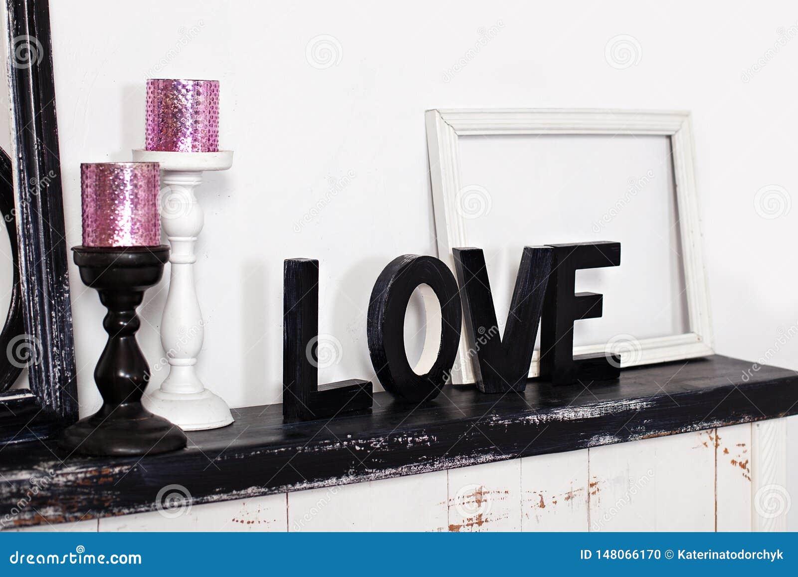 La palabra de madera es amor En la chimenea son dos palmatorias con las velas y el amor de madera de la palabra Inscripción del a