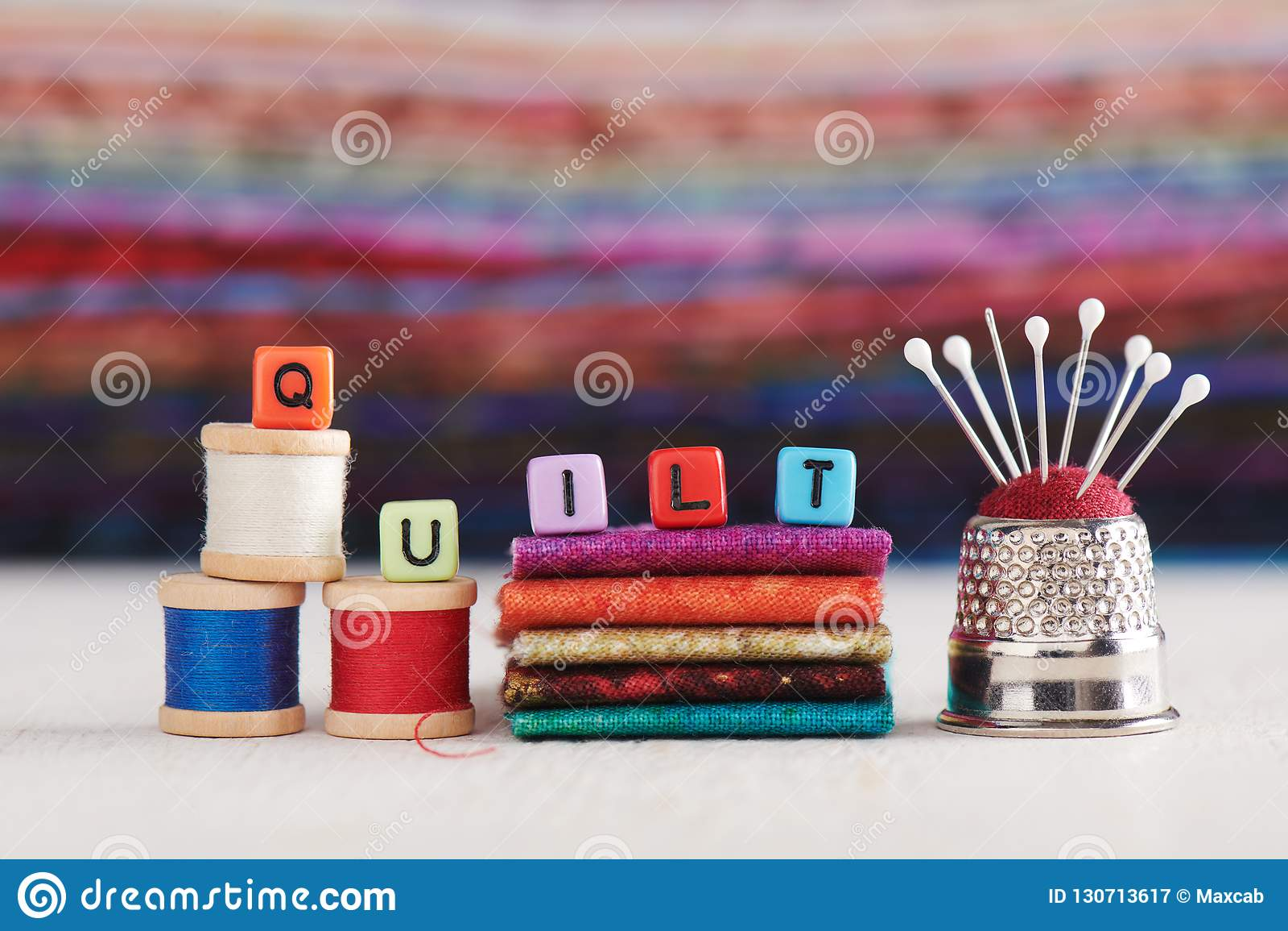 La palabra EDREDÓN se compone de los cubos de imitación de la joyería rodeó los accesorios de costura