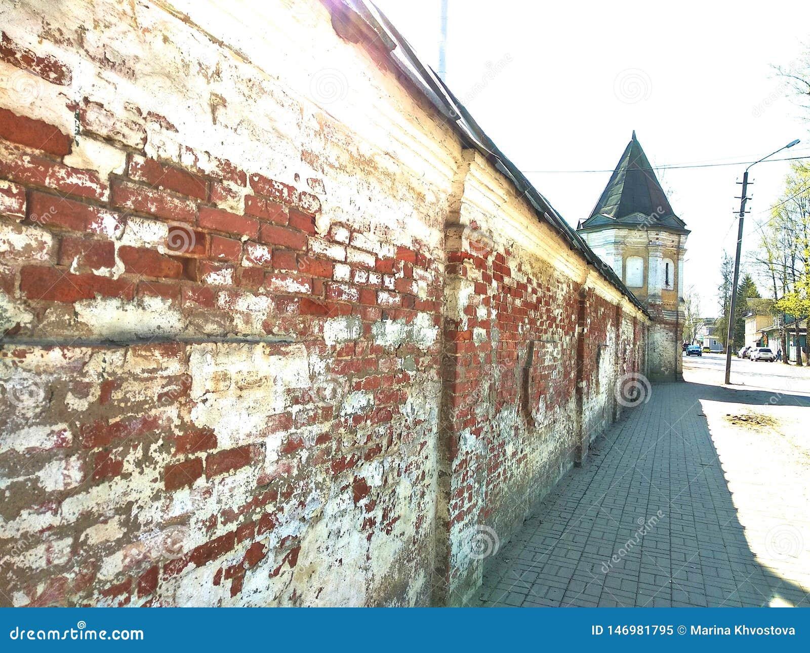La pared de ladrillo roja y blanca del monasterio con una pequeña ciudad en el centro de Rusia
