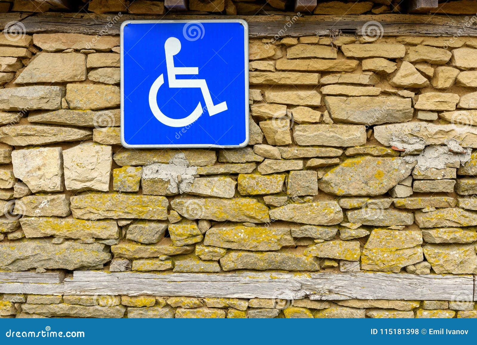 La parete di pietra e l accesso disabile firmano, handicappano il segno accessibile