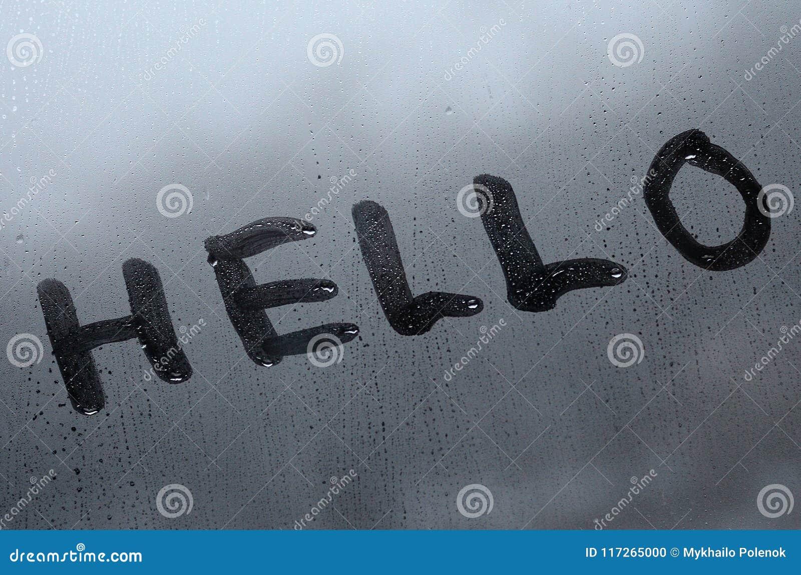 La parola inglese ciao è scritta con un dito sulla superficie del vetro appannato