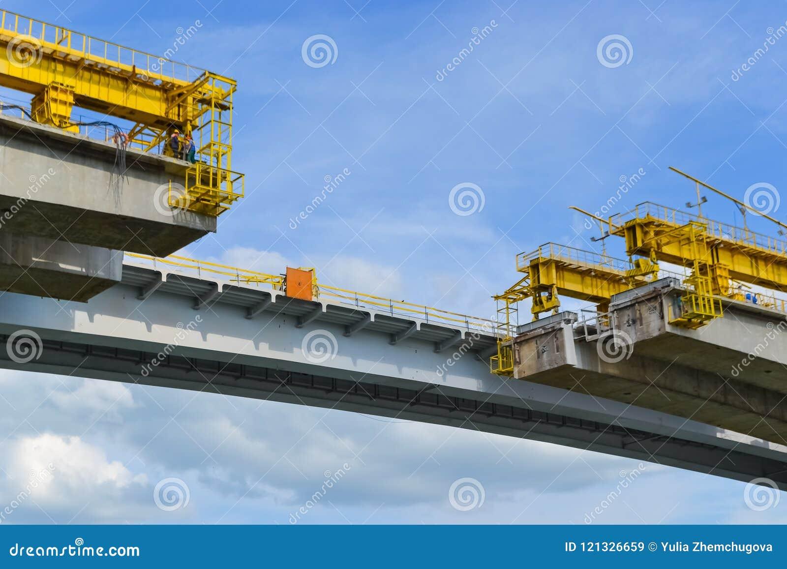 La parte non finita del ponte della strada sopra il fiume ricostruzione della parte della portata, lavoro ad altezza