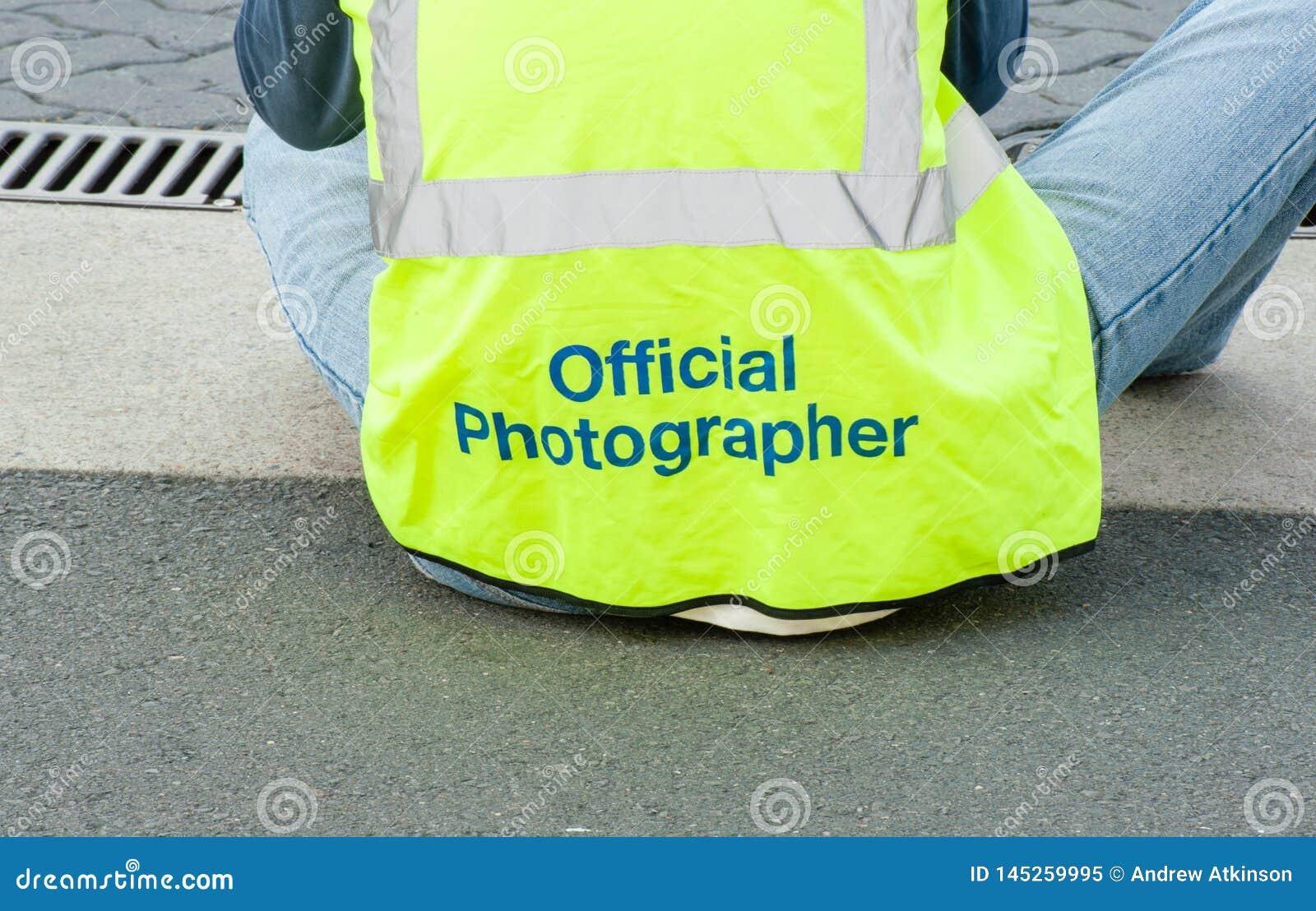 La parte posterior de una sentada oficial del fotógrafo, fotografiando un acontecimiento