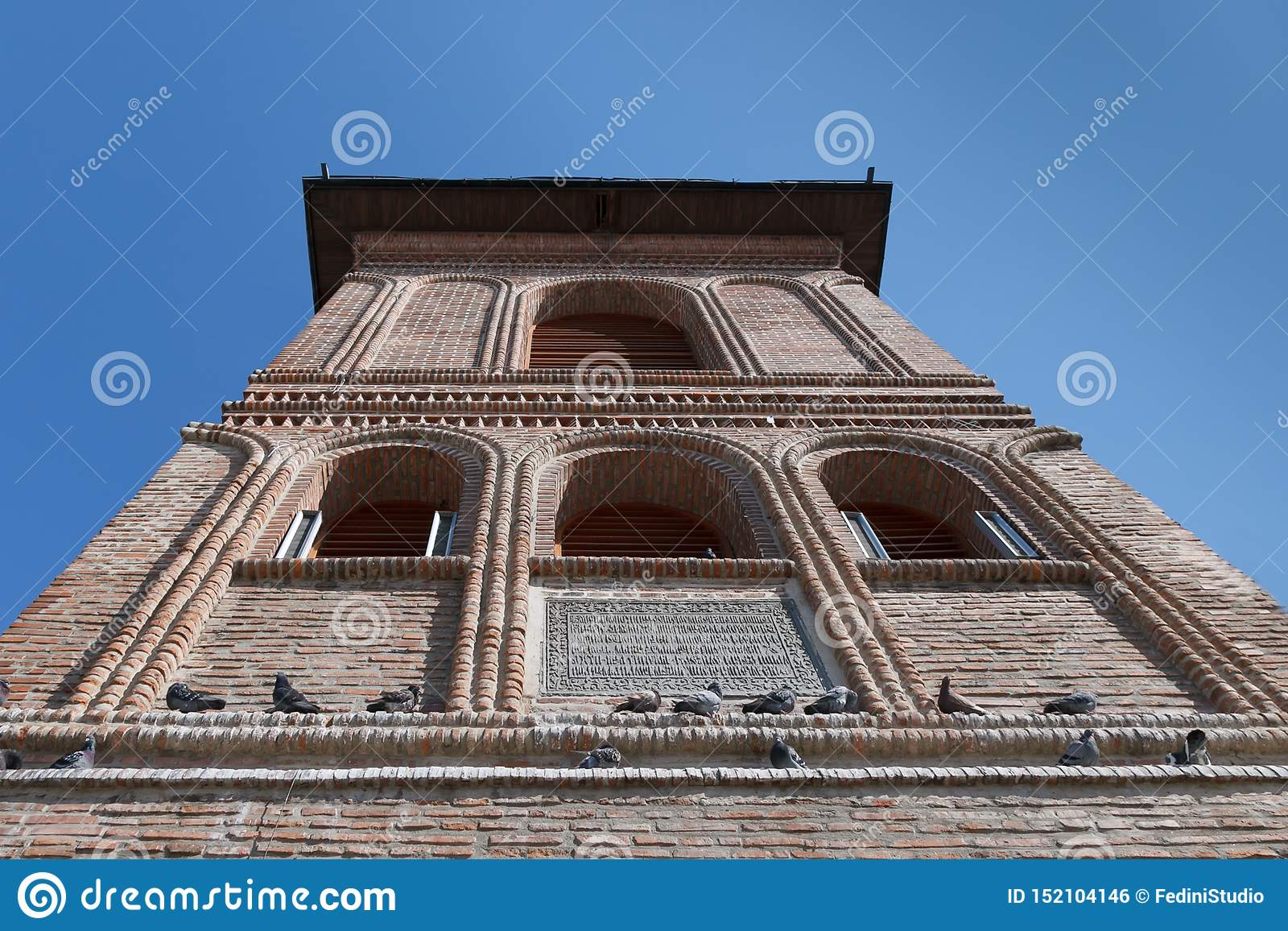 La parte superior de la fachada vieja del ladrillo del campanario con las palomas que se sientan Colina metropolitana, Bucarest,