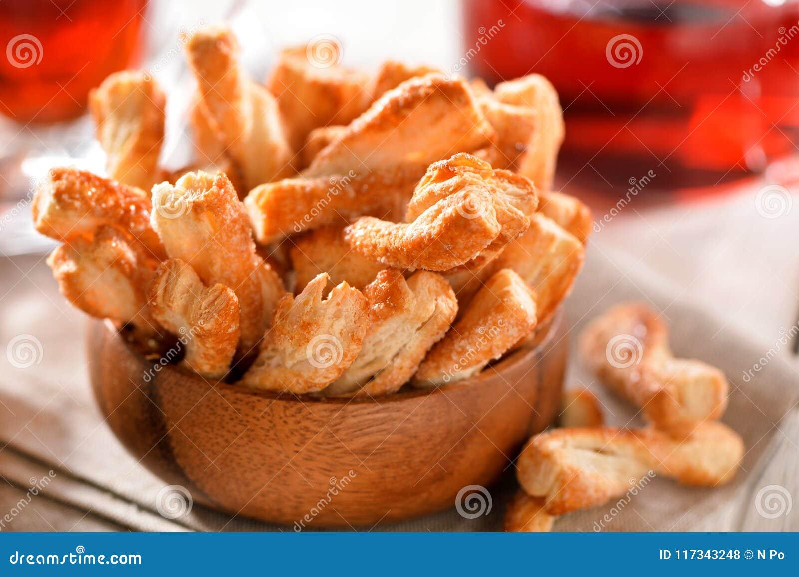 La pasta de hojaldre pega el primer de las galletas en cuenco de madera en la tabla