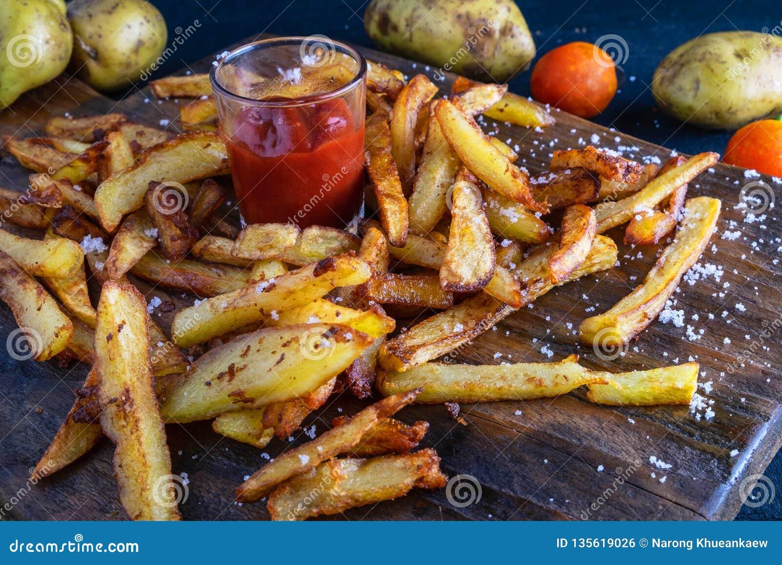 La patata cocida hecha en casa fríe con la salsa de tomate en la tierra trasera de madera