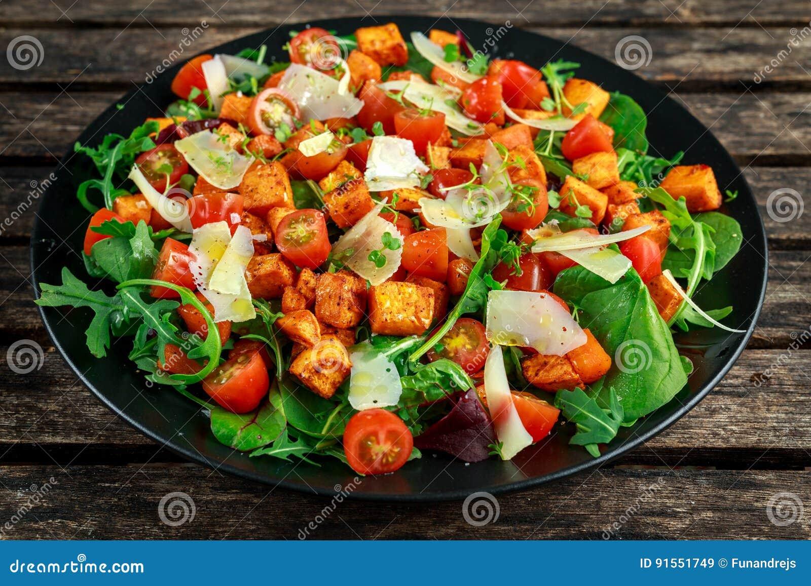 La patata dulce, las zanahorias, los tomates de cereza y la ensalada de cohete salvaje con el queso feta sirvieron en placa negra