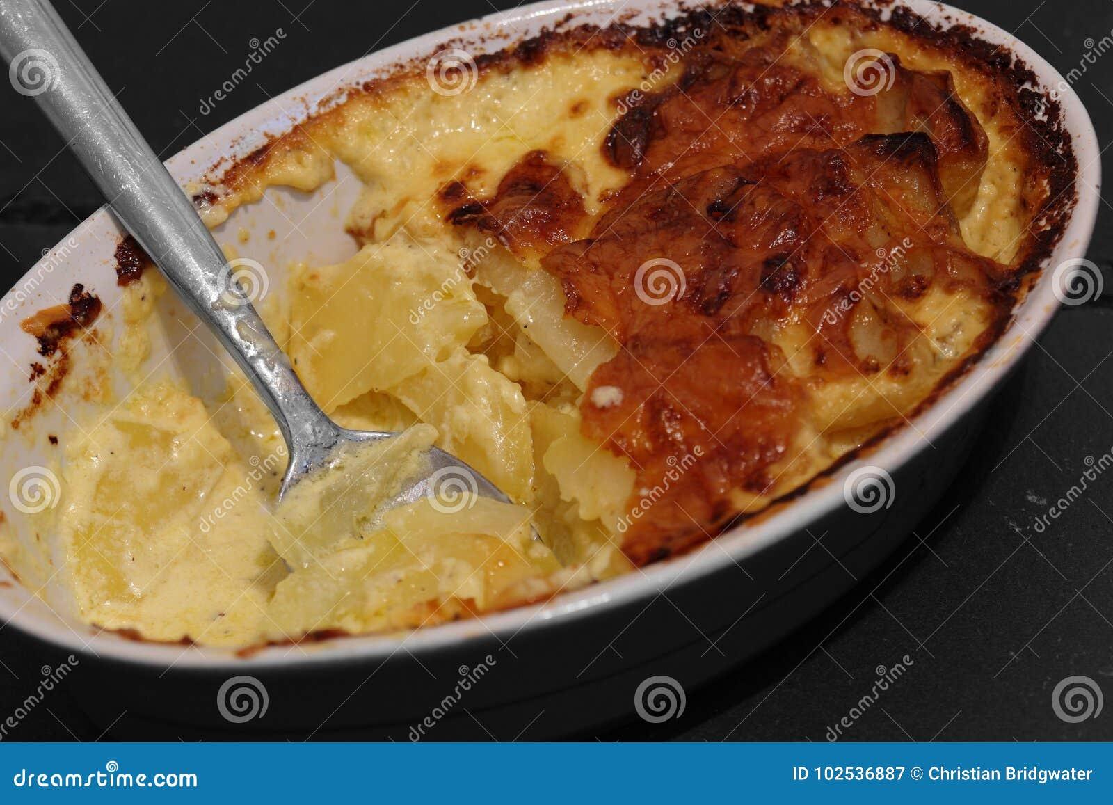Patata Porner la patata poner crema con queso coció en un plato en pizarra