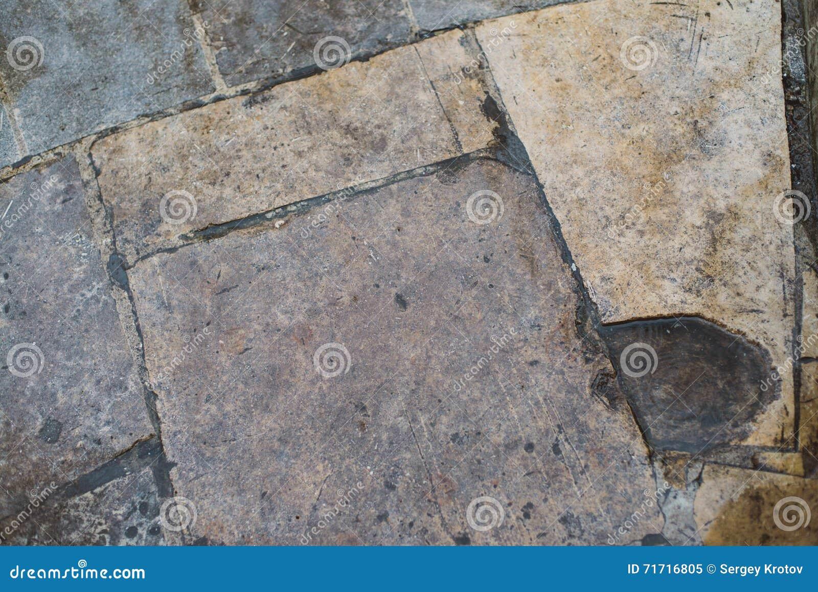 La pavimentazione in piastrelle di pietra ruvida con le crepe e le