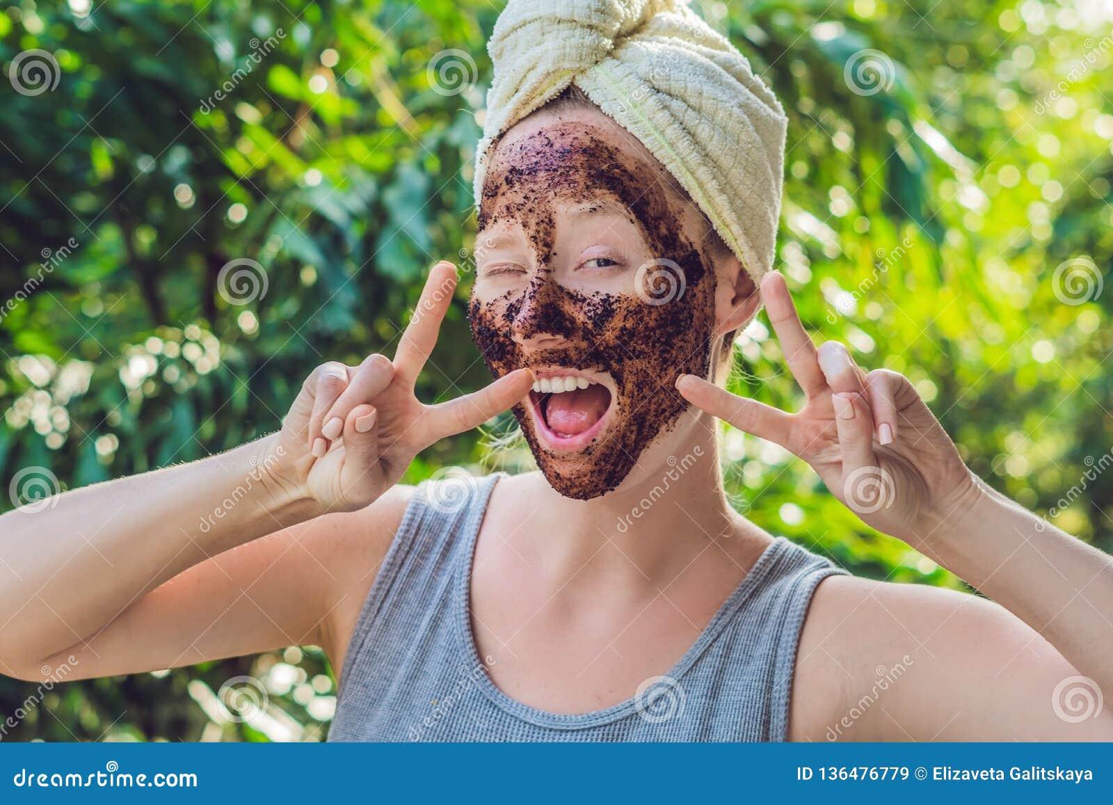 La pelle del fronte sfrega Il ritratto della maschera di modello femminile sorridente sexy di Applying Natural Coffee, fronte sfr