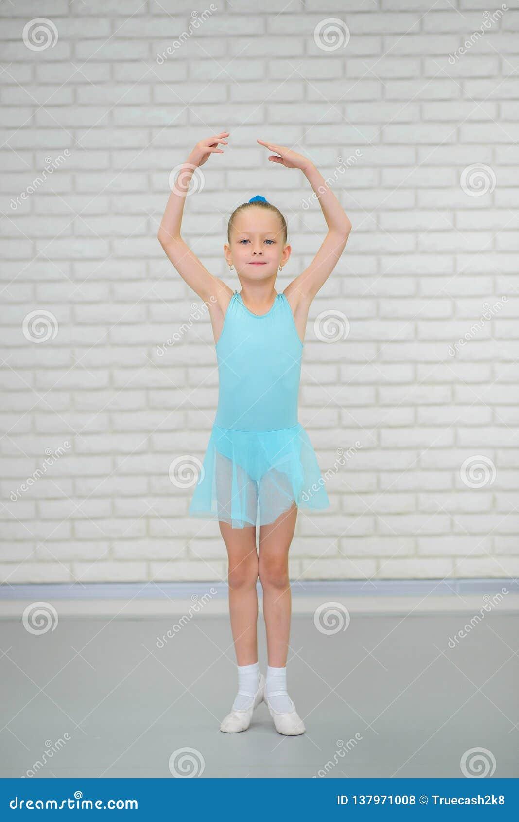 La pequeña bailarina en zapatos azules del vestido y del pointe está bailando en escuela del ballet Muchacha linda en clase de da