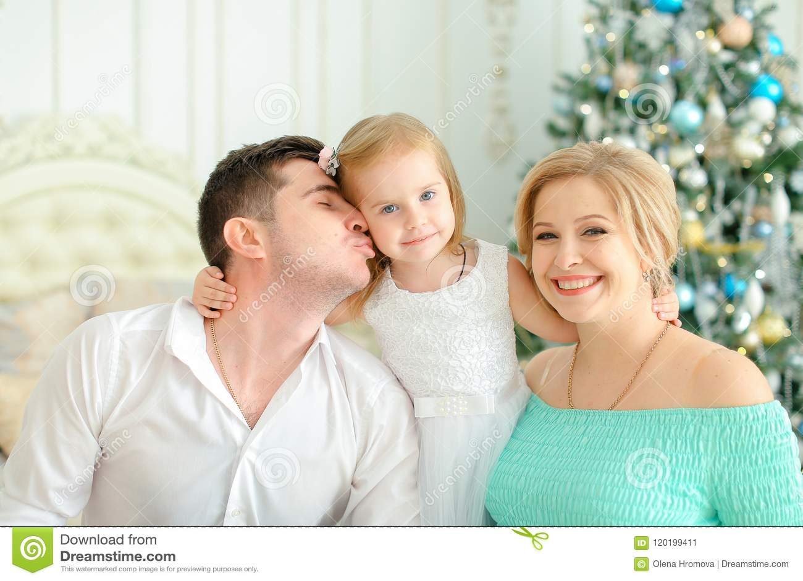 La pequeña hija que se sentaba con besar el padre y a la madre rubia cerca adornó el árbol de navidad
