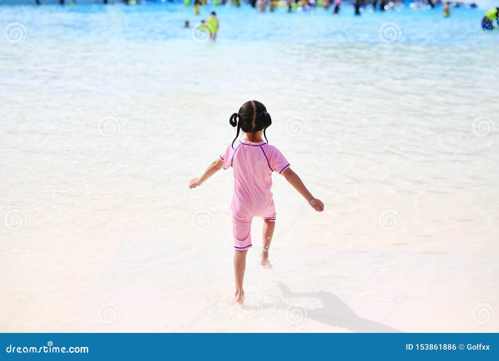 La pequeña muchacha asiática del niño goza y funcionamiento en la piscina grande al aire libre el días de fiesta Niños de la vist