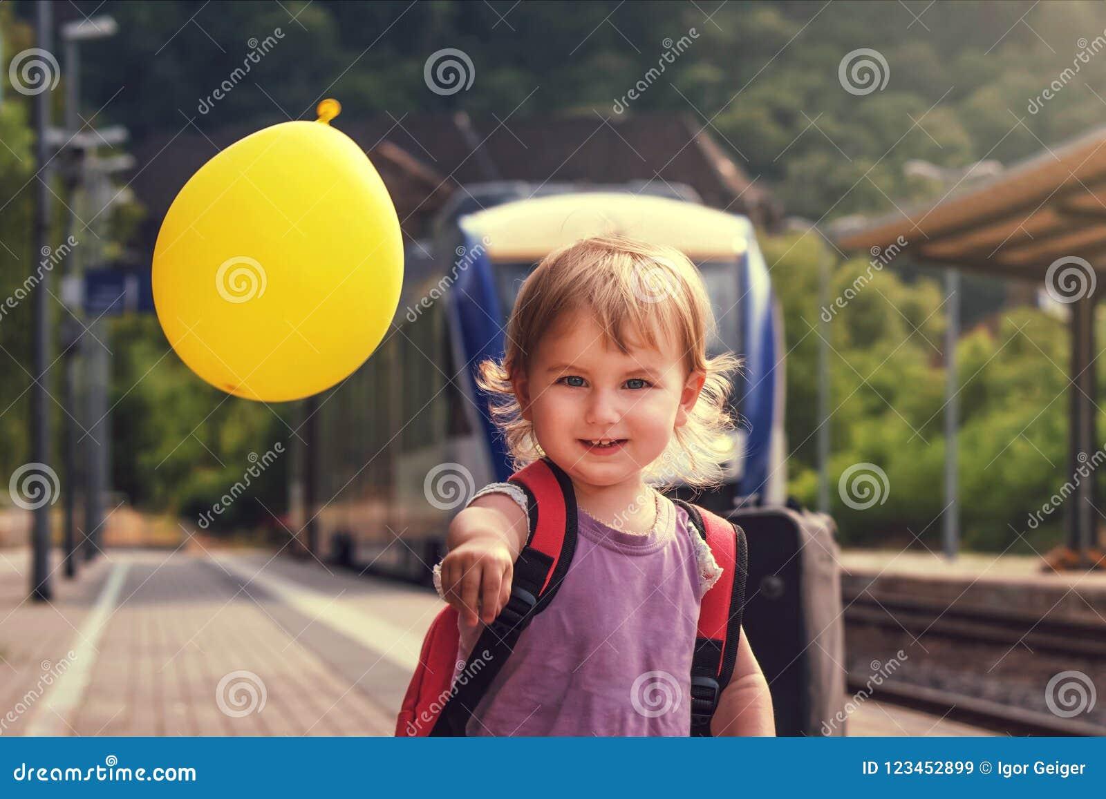 La pequeña muchacha bonita camina a lo largo de la plataforma de la estación del tr