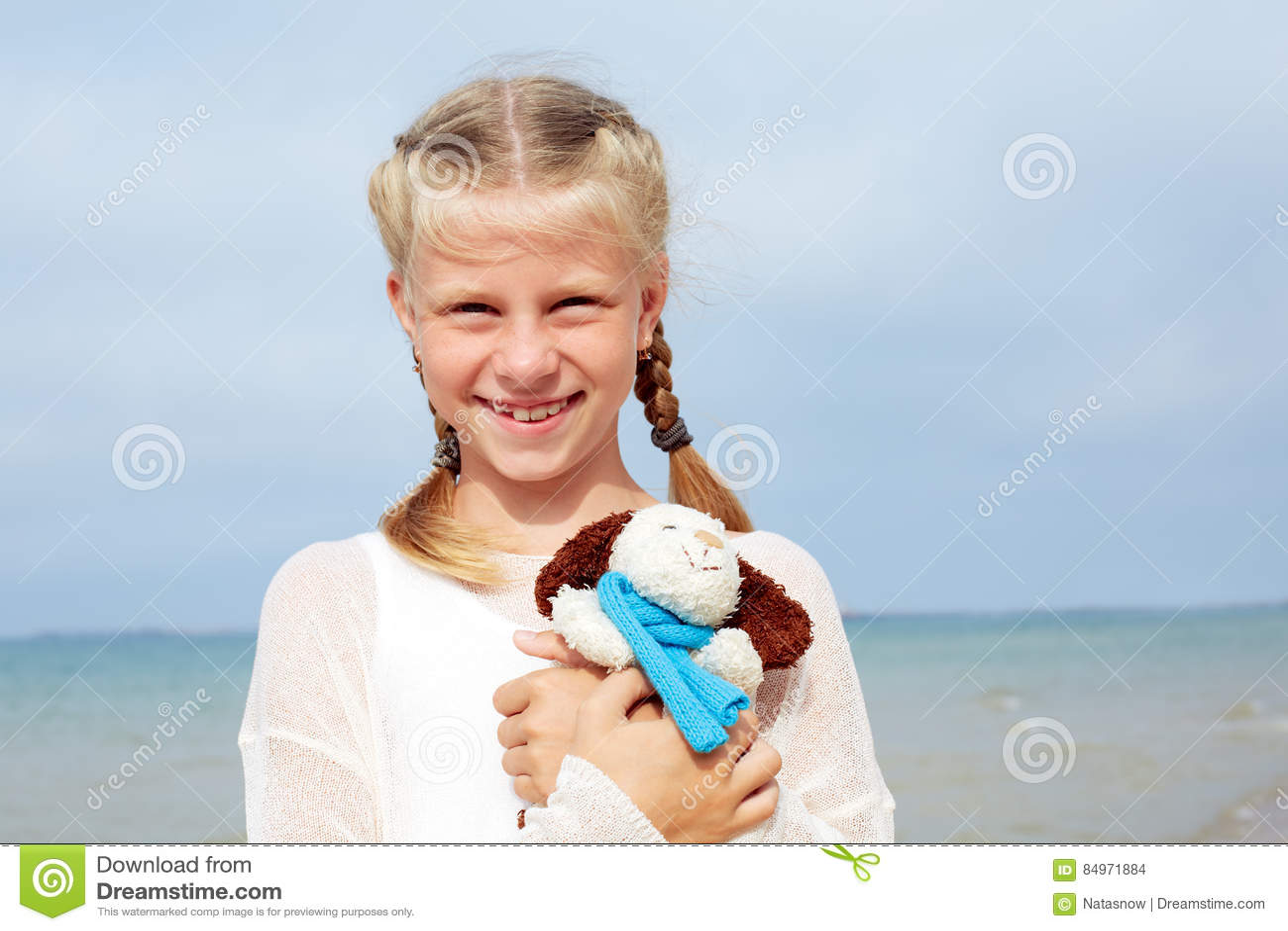 La pequeña muchacha hermosa abraza un perro-juguete graciosamente